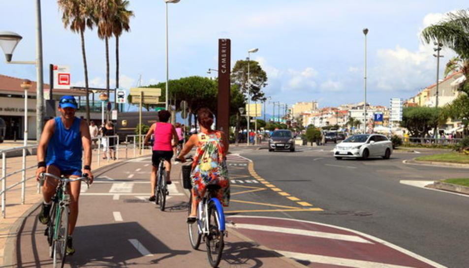 Turistes en bicicletes al Passeig Marítim de Cambrils on es va produir l'atemptat terrorista ara fa un any.