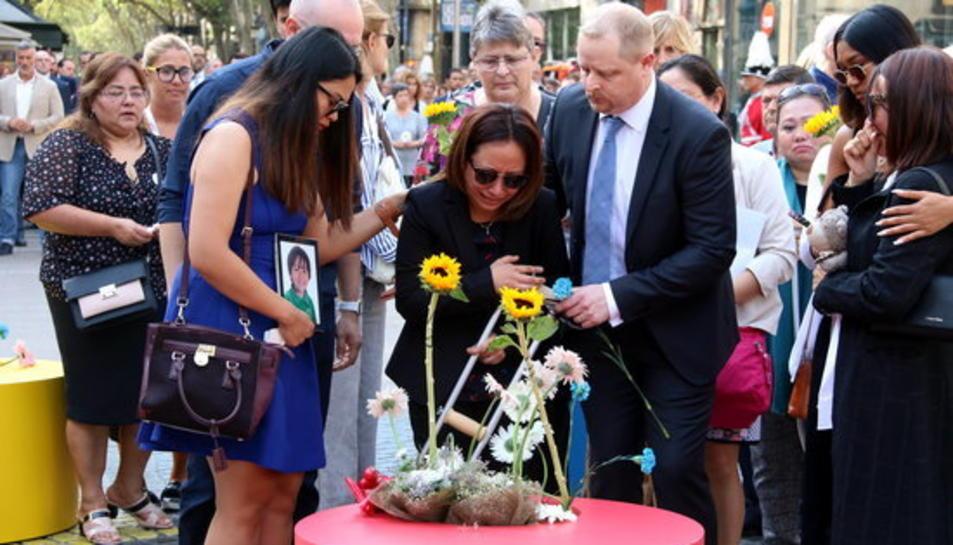 Familiars de les víctimes dels atemptats del 17-A fent l'ofrena floral al mosaic de Joan Miró de la Rambla de Barcelona.