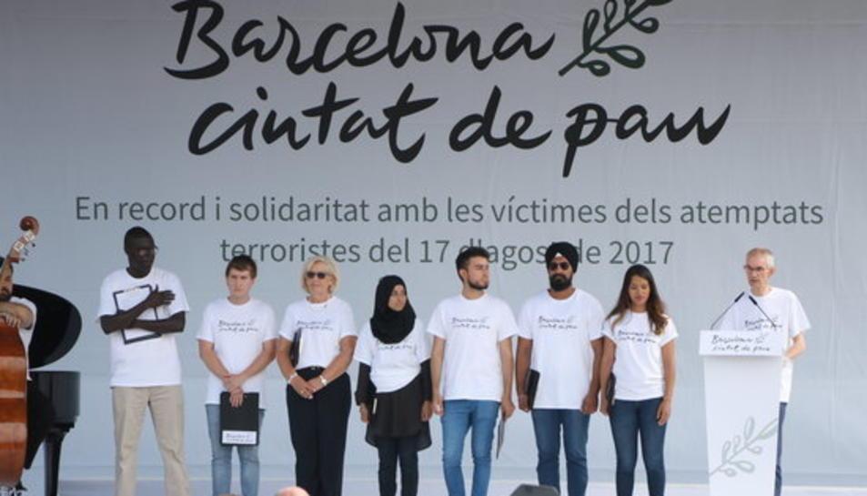 Pla general de l'escenari de plaça Catalunya on hi ha les vuit persones encarregades de llegir el manifest en record de les víctimes del 17-A.