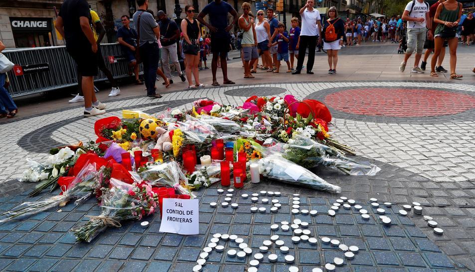 Rams de flors i objectes de tot tipus dipositats al mural de Miró de la rambla de Barcelona en record a les víctimes dels atemptats.