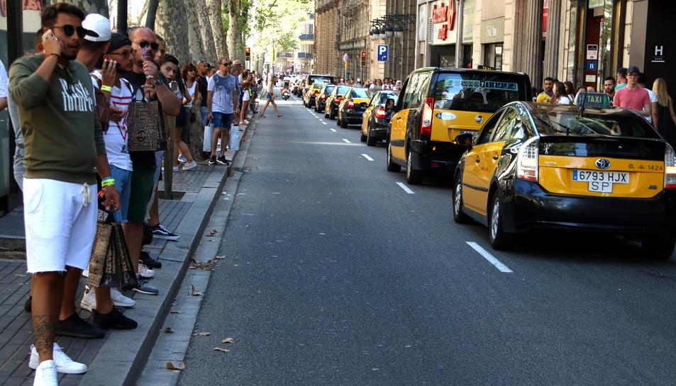 Taxis baixant per la Rambla en marxa lenta, en solidaritat amb les víctimes dels atemptats del 17-A.
