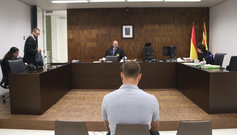 Pla mitjà d'Andreu Curto, d'esquena, assegut durant el judici a la Ciutat de la Justícia.