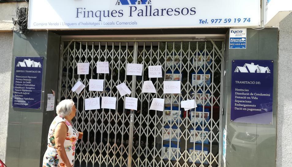 Una veïna llegeix el contingut dels cartells col·locats a la tanca de l'antiga oficina de les finques.