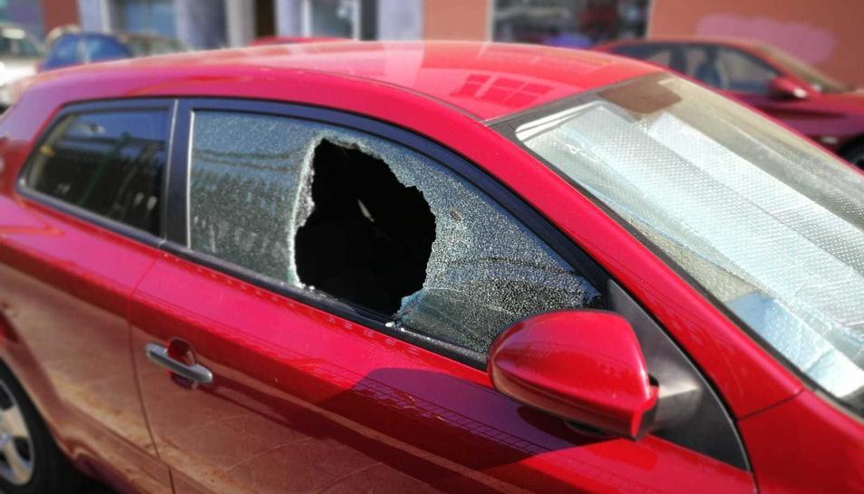 Un dels cotxes afectats, amb el vidre del copilot totalment trencat.