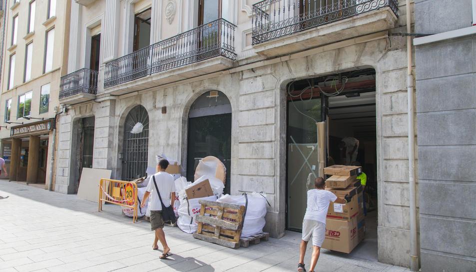 Un operari introdueix material en la que serà la nova oficina de CaixaBank a la Rambla Nova.