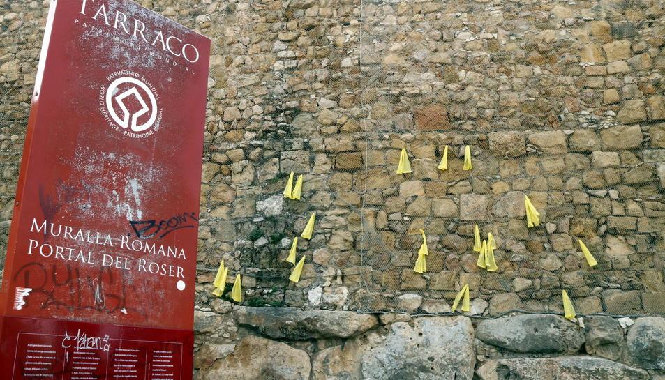 Pla mig de la Muralla de Tarragona amb llaços grocs i un cartell informatiu en primer terme.