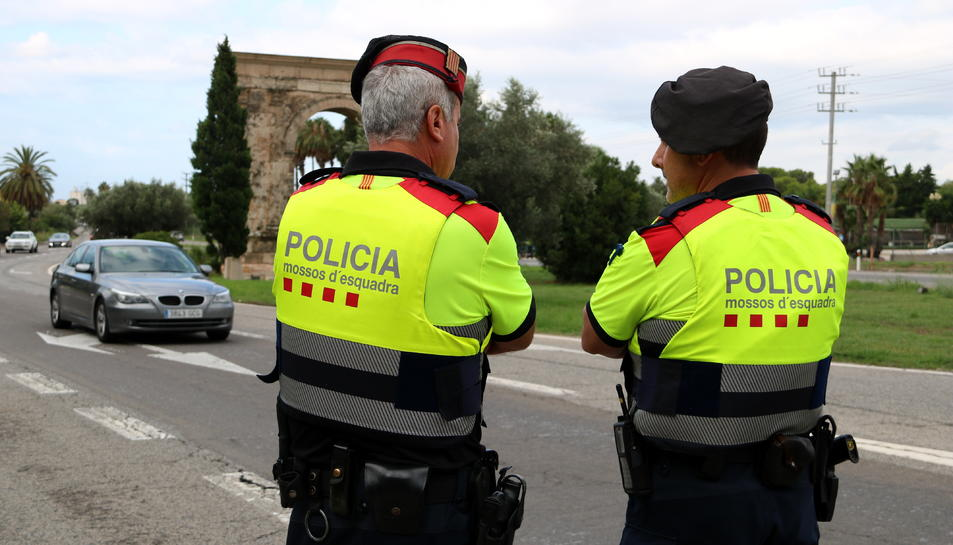 Pla mig de dos agents dels Mossos d'Esquadra en el control informatiu a l'Arc de Berà.