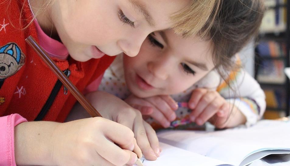 Nenes treballant juntes en una activitat extraescolar.