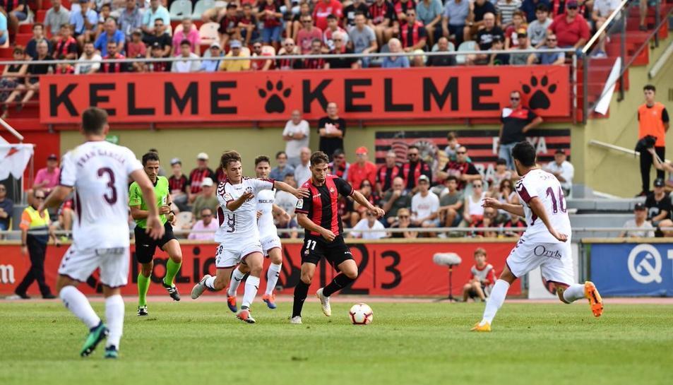 Fran Carbia conduint l'esfèrica rodejat de defensors