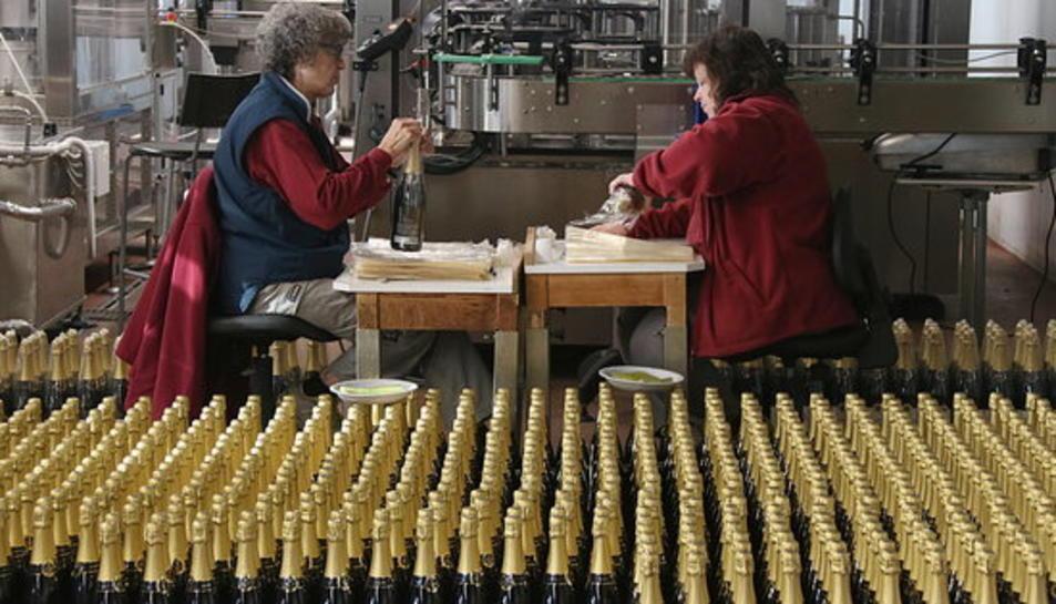 Dues treballadores embolicant ampolles de cava per la campanya de Nadal.