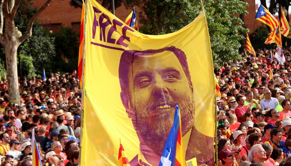Una pancarta que porta escrit 'Free' amb la cara d'Oriol Junqueras alçada al mig de la manifestació de la diada convocada per l'ANC.