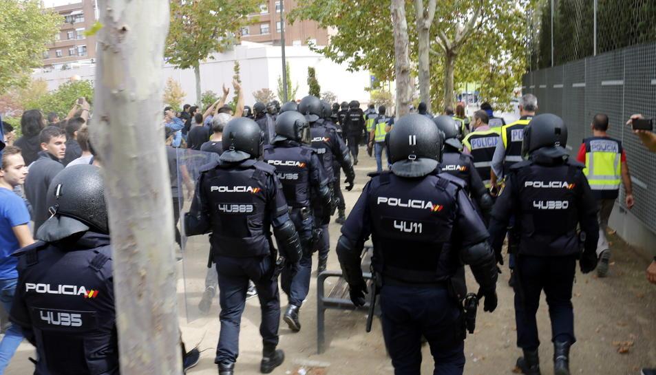Agents de la policia espanyola marxant amb les urnes de l'IES Ronda de Lleida.