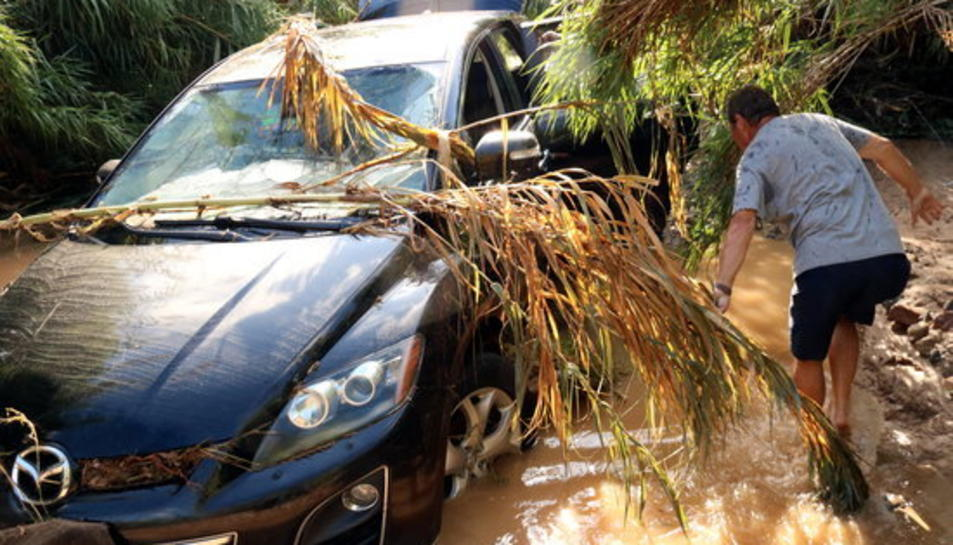 El Celestino, observant el seu cotxe que va abandonar amb la seva dona quan creuaven la riera de Maspujols.