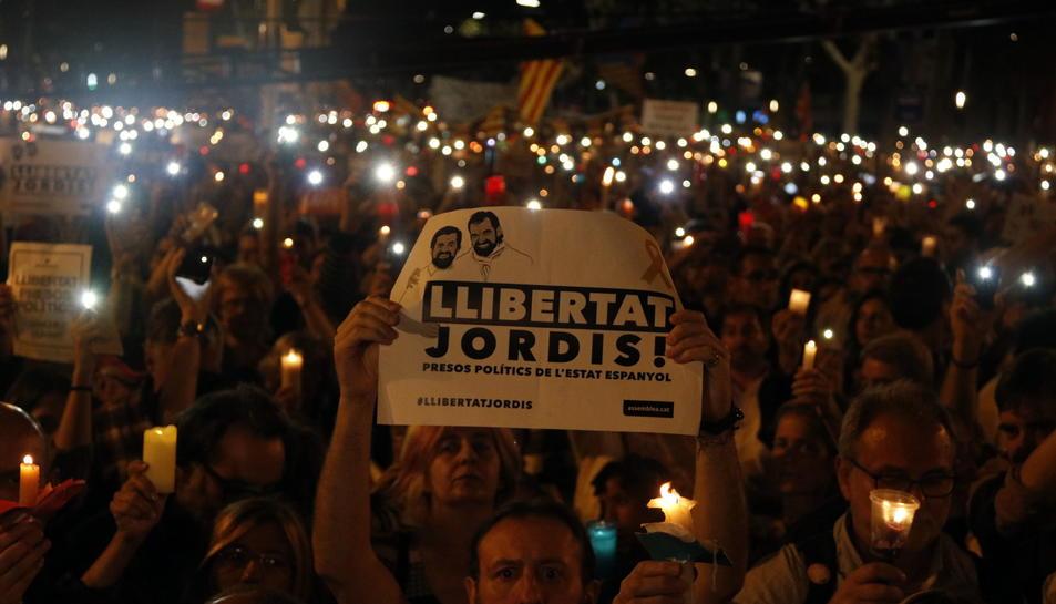 Un home sosté una pancarta de 'Llibertat Jordis' i, al seu voltant, persones amb espelmes enceses.