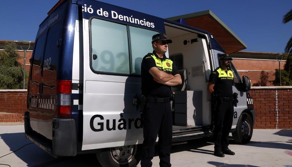 Pla obert de dos agents de la Guàrdia Urbana de Tarragona al costat d'una oficina mòbil de denúncies, davant el centre cívic de Torreforta. Imatge del 23 d'octubre del 2018