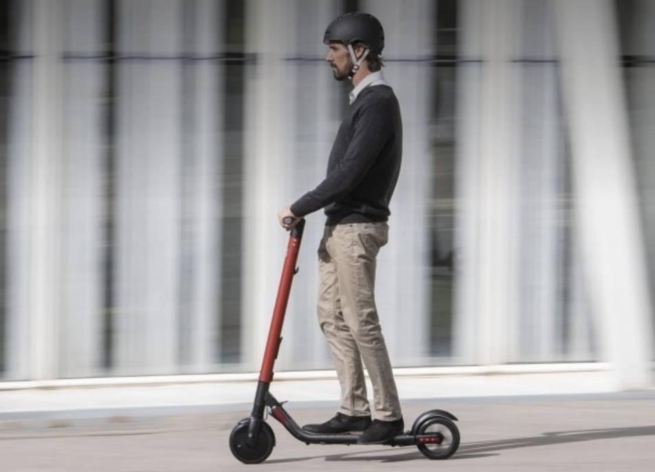 Un home viatje en patinet elèctric.