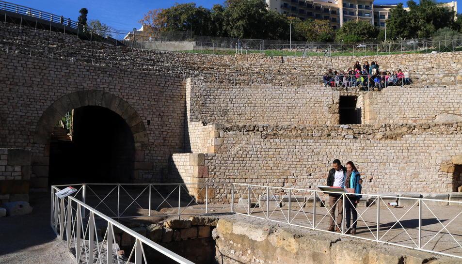 Dos turistes visitant l'amfiteatre romà de Tarragona amb un grup d'escolars assegut a la graderia.