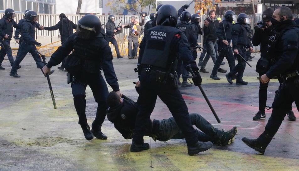 Dos agents dels Mossos, arrossegant un manifestant antifeixista a la plaça U d'Octubre de Girona.