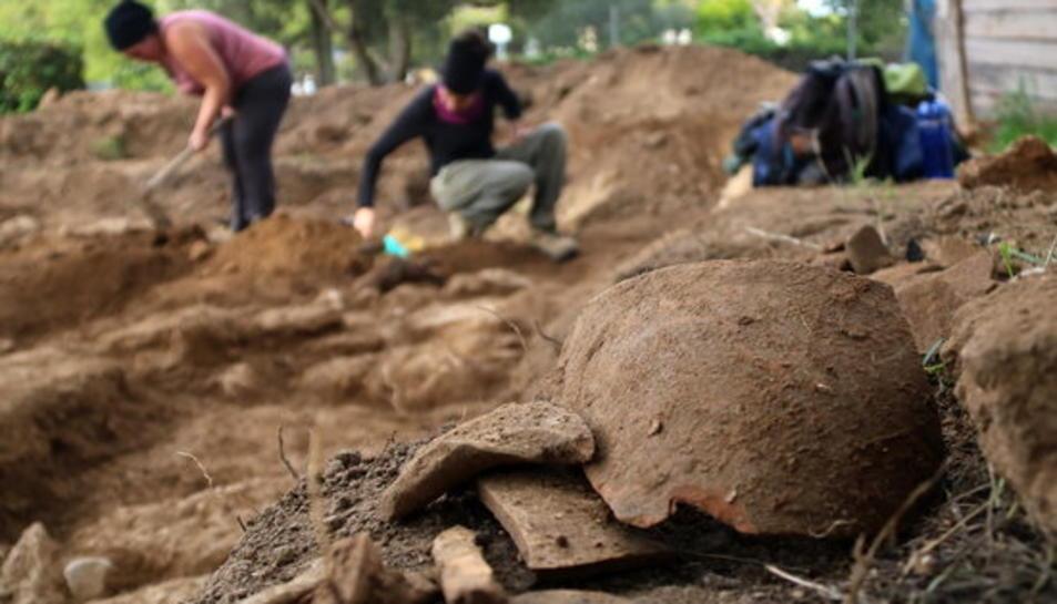 Restes de ceràmica trobades en un gran jaciment iber a Cubelles, amb els arqueòlegs treballant al fons.