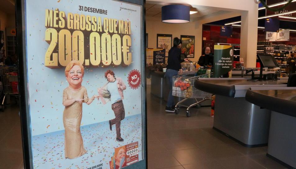 Un plafó amb un cartell de la Grossa de Cap d'Any en un supermercat.