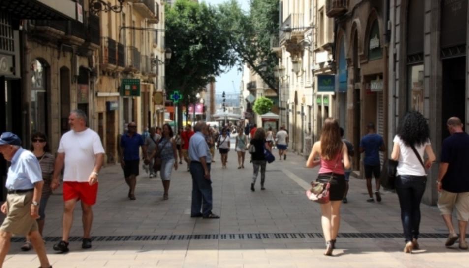 Pla general de gent passejant i comprant en un carrer de Tarragona.