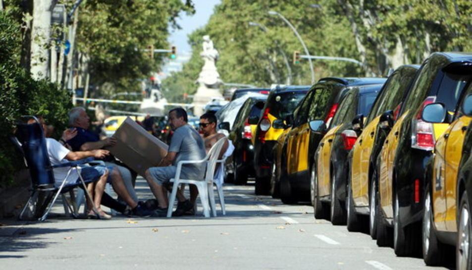 Imatge d'arxiu d'un grup de taxistes en vaga, asseguts amb cadires i taules a la Gran Via el passat mes de juliol.