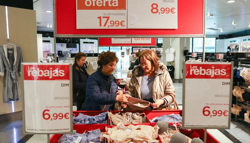 Dues dones miren llenceria de roba en uns grans magatzems de la ciutat.