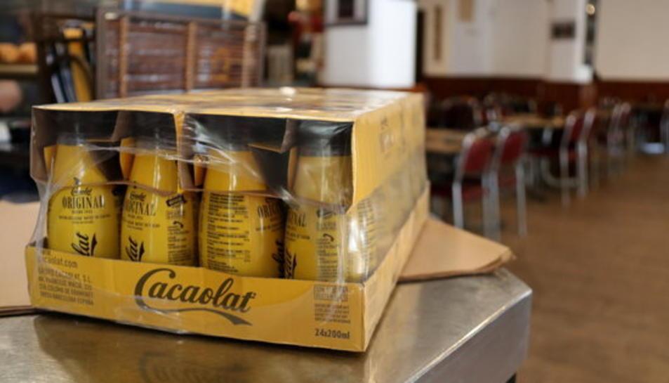 Pla detall d'un paquet d'ampolles de Cacaolat damunt la barra d'un bar.