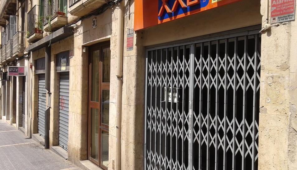 Imatge d'un carrer del centre de la ciutat amb locals tancats.