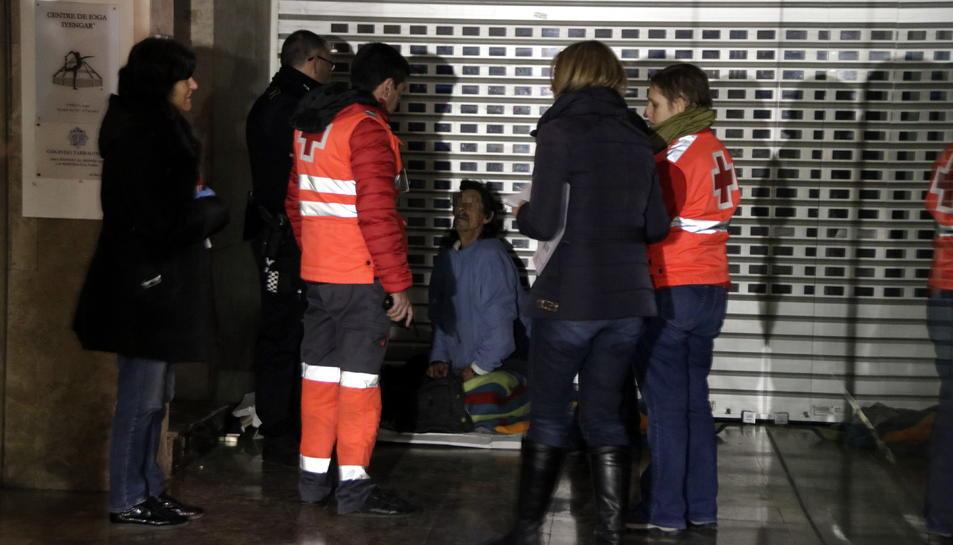 Pla obert de voluntaris de la Creu Roja i de membres de Serveis Socials atenent un sensesostre que dorm a l'entrada d'una botiga del carrer Unió de Tarragona. Imatge de l'11 de gener del 2018