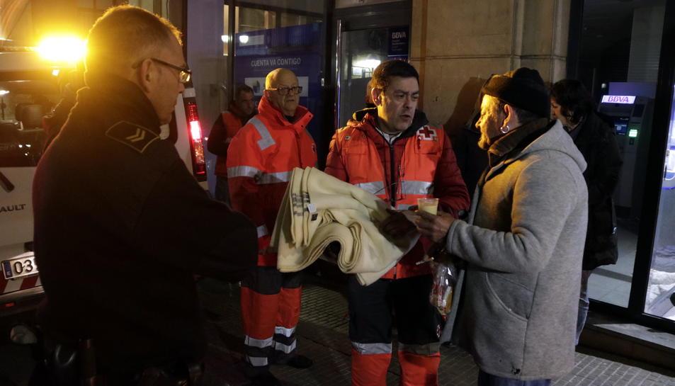 Pla americà de voluntaris de la Creu Roja lliurant una manta i un got de caldo a en Francisco Moreno, un sensesostre que passa la nit en un caixer de Tarragona. Imatge de l'11 de gener del 2018