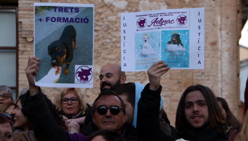 Dos manifestants alçant cartells reivindicatius en la protesta per la mort d'un rottweiler abatut per la Policia Local de Calafell.