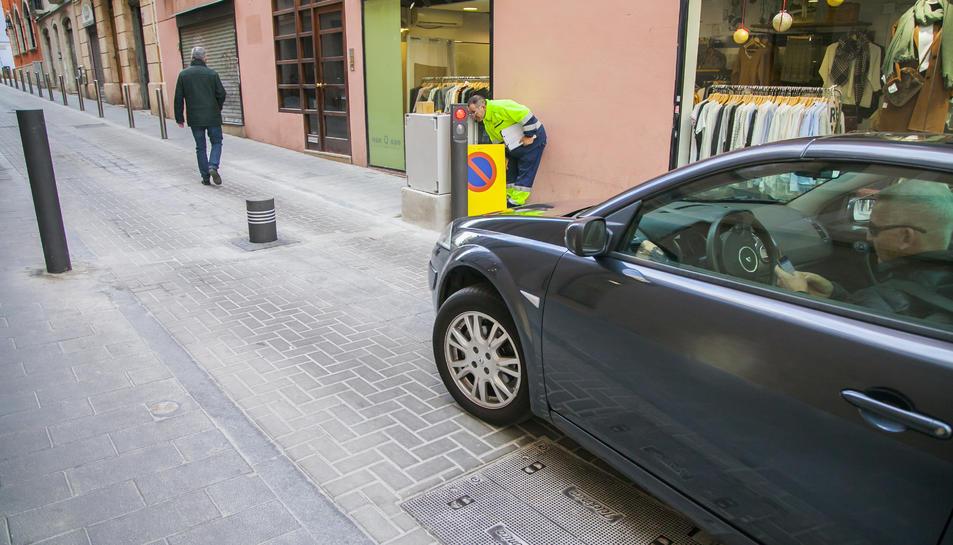 Manuel Salines, usuari d'una plaça de pàrquing, marca el número de telèfon per abaixar la pilona.