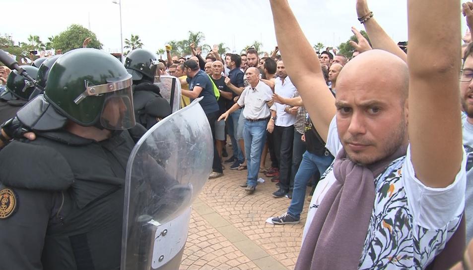 Gent amb les mans en alt davant dels antiavalots de la Guàrdia Civil a la Ràpita, l'1 d'octubre de 2017.