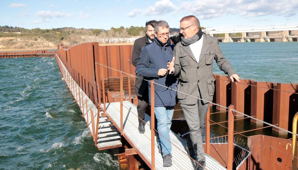 Pla general del secretari d'Estat de Medi Ambient, Hugo Morán, a l'esquerra, acompanyat per l'alcalde de Flix, Marc Mur, en la visita a la represa de les obres de descontaminació del pantà de Flix. Imatge del 28 de gener de 2019