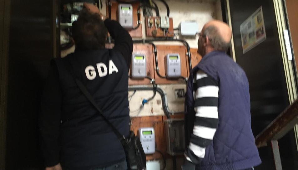 Els operaris inspeccionant els comptadors de llum de l'edifici ahir al matí.