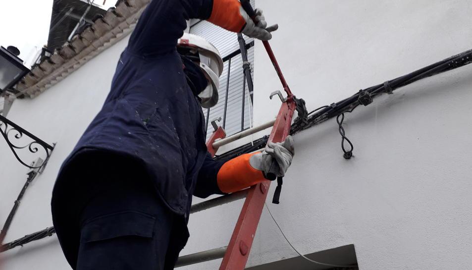 Un treballador d'Endesa, tallant una escomesa elèctrica, per evitar el frau.