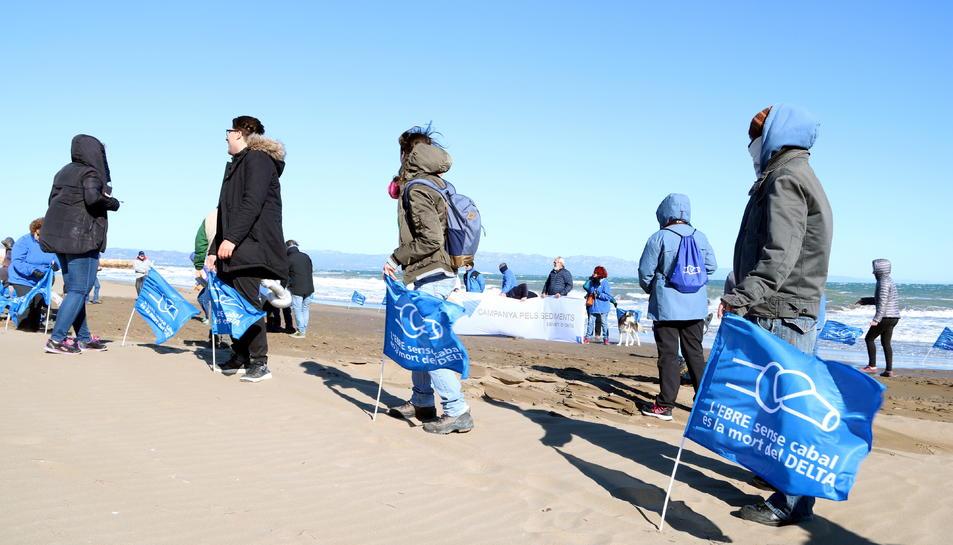 Els ecologistes al costat de les banderes que han col·locat a la platja de la Marquesa per visualitzar la regressió del delta de l'Ebre.