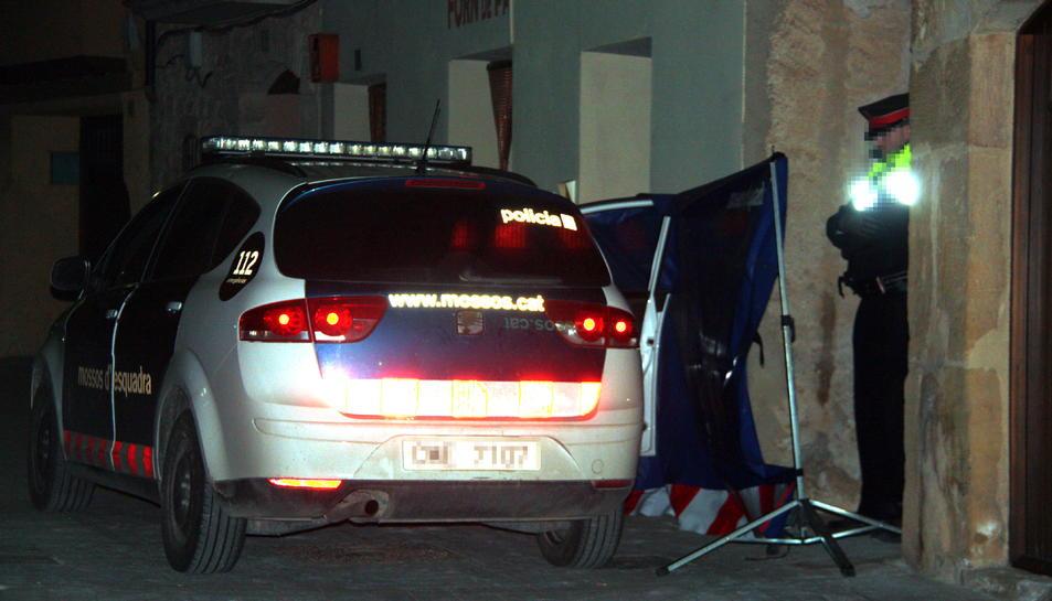 Un vehicle dels Mosso d'Esquadra i un agent custodiant l'entrada a la casa on s'ha produït l'incendi mortal a Arnes.