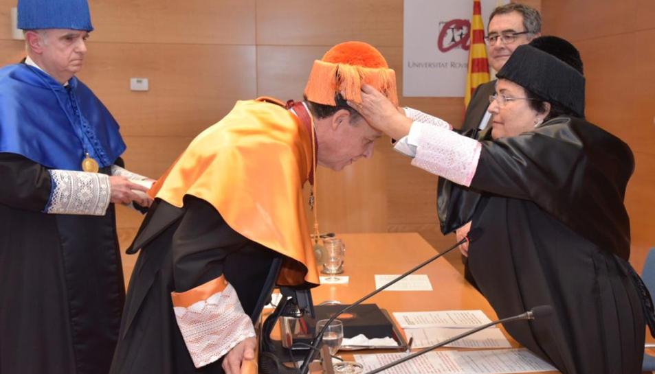 La rectora de la URV, Maria José Figueras, posant el birret al nou doctor honoris causa, Xavier Prats.