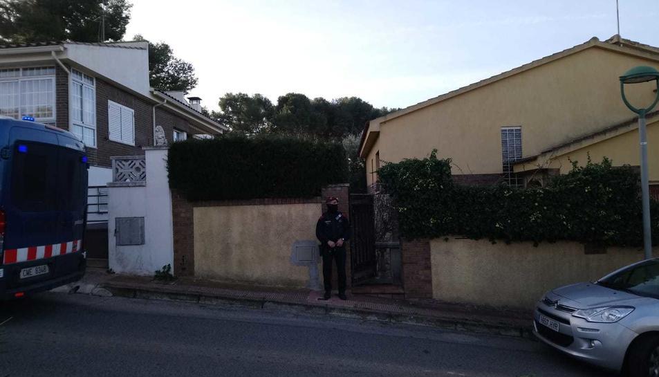 Imatge d'un agent davant d'un dels domicilis on s'estan fent entrades als Monnars.
