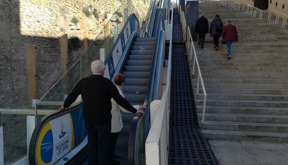 Dues persones dubten a pujar per les escales espatllades i altres tres fan el tram afectat a peu.