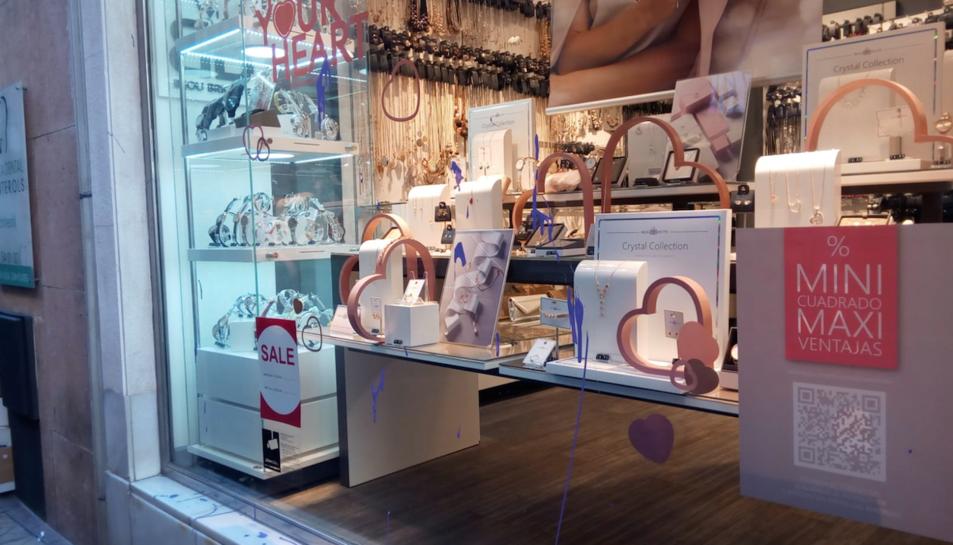 Imatge d'una de les botigues afectades amb pintura de color lila a l'aparador.