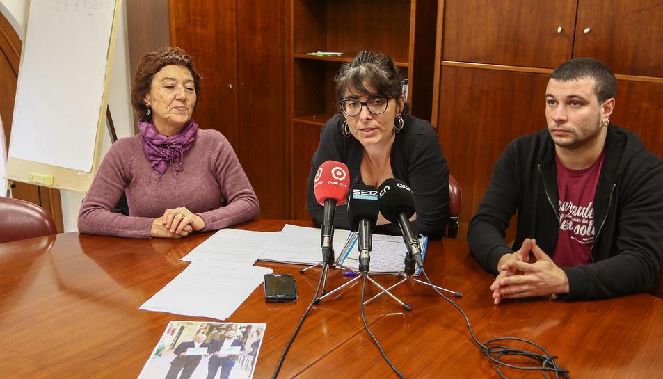 Membres de la CUP de Reus, Marta Llorens, Mariona Quadrada i Edgar Fernández, mostrant una foto de l'acalde i cap de llista del PDeCAT, Carles Pellicer, i el cap de campanya, Marc Just.