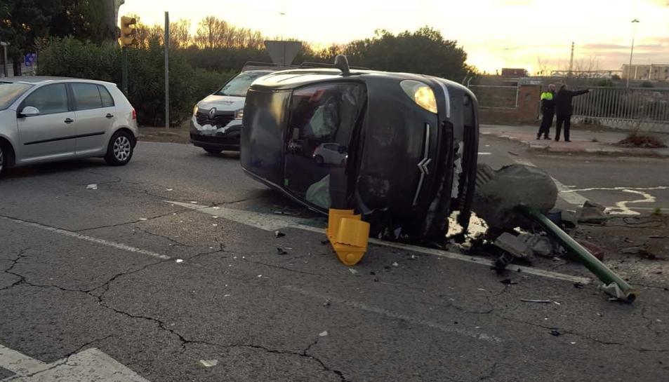 Imatge del cotxe bolcat junt al semàfor contra el qual ha col·lidit.
