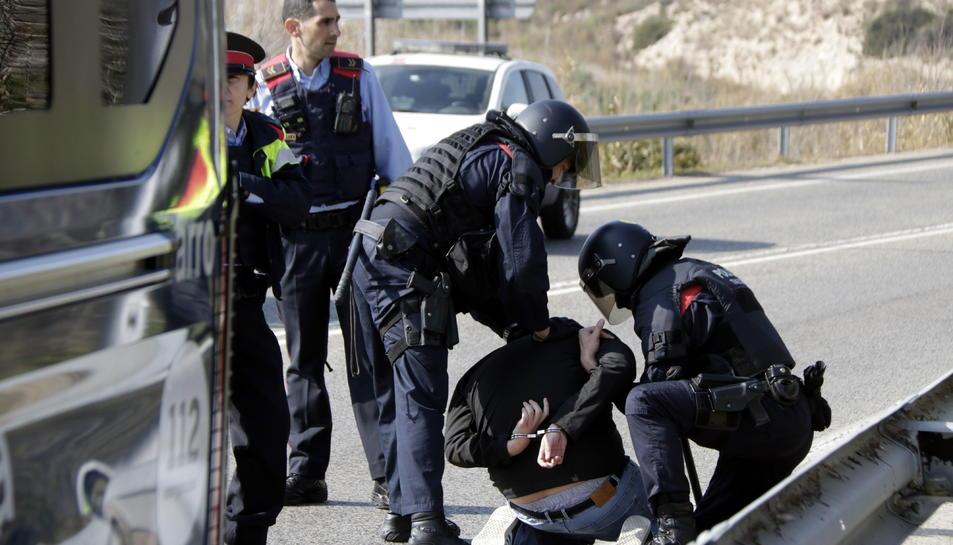 Pla obert del noi detingut pels Mossos d'Esquadra, d'esquenes i emmanillat, a les proximitats del peatge de l'AP-7 a Tarragona. Imatge del 21 de febrer del 2019