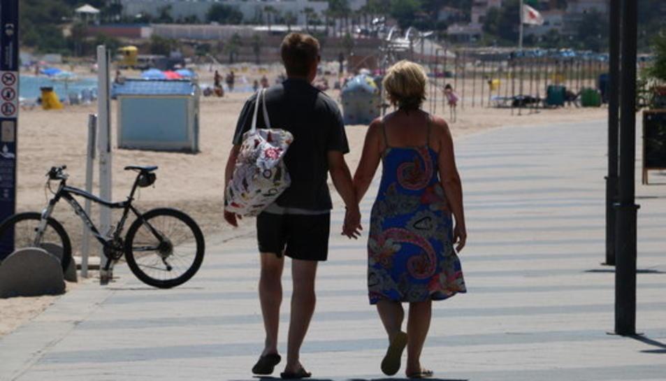 Dos turistes d'esquena passejant pel passeig marítim de Torredembarra.