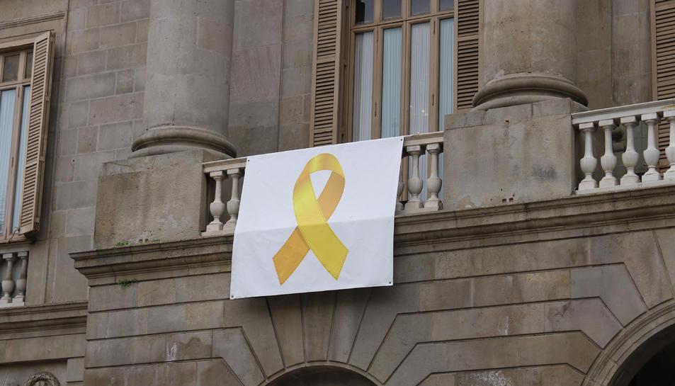 Pla mig de la pancarta amb el llaç groc que hi ha a la façana de l'Ajuntament de Barcelona.