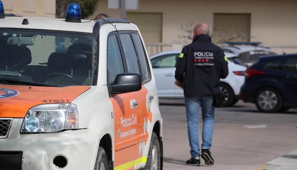 Un vehicle de protecció civil a Deltebre amb un agents dels Mossos sortint de l'Ajuntament amb caixes de documentació.
