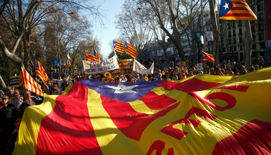 Imatge de l'estelada, en primer terme, i els manifestants a Madrid amb cartells i senyeres.
